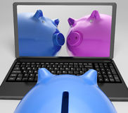 Piggybanks On Notebook Showing Online Transactions Royalty Free Stock Photo