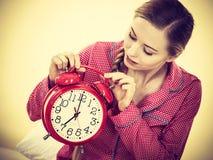 Pigiami d'uso della donna sonnolenta che tengono orologio Fotografia Stock