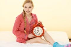 Pigiami d'uso della donna sonnolenta che tengono orologio Immagine Stock Libera da Diritti