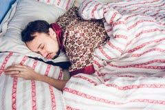 Pigiami dell'uomo addormentati a letto Fotografia Stock Libera da Diritti