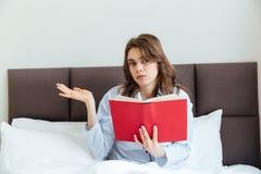 Pigiami della giovane donna confusa e di tenuta libro d'uso a letto Immagini Stock Libere da Diritti