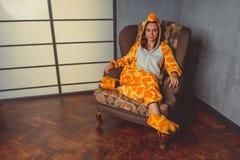 Pigiami per Halloween sotto forma di canguro Ritratto emozionale di una ragazza su un fondo del sofà Uomo pazzo e divertente in u immagine stock libera da diritti