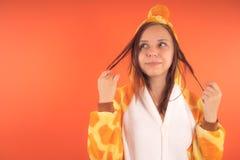 Pigiami sotto forma di giraffa ritratto emozionale di una ragazza su un fondo arancio donna pazza e divertente in un vestito anim immagini stock libere da diritti