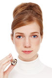 Pigmentation. Young red-haired girl with freckles holding quail egg in her hand, on white background Stock Image