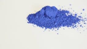 Pigmento blu isolato sopra bianco che fila intorno video d archivio