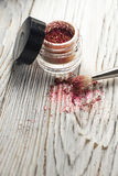 Pigments, glitter, brushes. Studio photo on a wooden background Stock Images