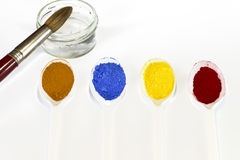 Pigments powder with a bowl of water and a brush Royalty Free Stock Photos