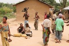 Pigmeos que bailan y que juegan en las latas. Imagen de archivo