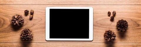 Pigne e compressa digitale con lo schermo vuoto sulla tavola di legno Tema online di acquisto di Natale fotografia stock libera da diritti