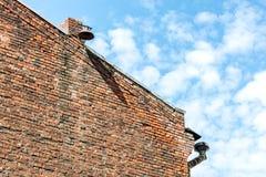 Pignon de mur de briques avec le vieux drain et lanterne sur la cheminée encore Images stock