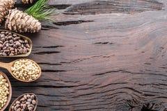 Pignons dans le cône de pignon de cuillère et sur la table en bois Aliment biologique photographie stock