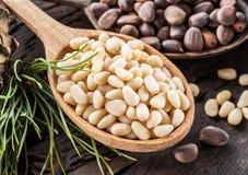 Pignons dans le cône de pignon de cuillère et sur la table en bois Aliment biologique image stock