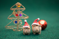 Pigs wearing christmas hat. Two pigs wearing christmas hat stand on green background royalty free stock photo