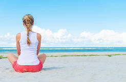 Pigtailed girl sitting on the beach. Stock Photos