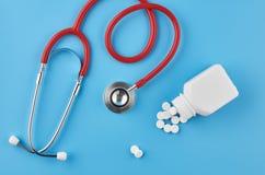 Pigułek pastylek kapsuł zbliżenie Na błękitnym tle, słój medycyna Na błękitnym tle, słoju medycyna i stetoskopie, fotografia royalty free