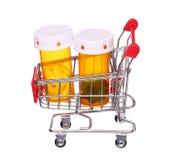 Pigułki butelka w wózek na zakupy na bielu Zdjęcie Royalty Free