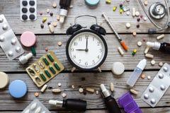 Pigułki i zegar na stole, odgórny widok Zdjęcia Royalty Free