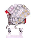 Pigułki w wózek na zakupy na bielu Fotografia Stock
