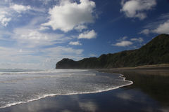 Piha Beach. Is a famous surf beach, situated on the west coast of the North Island, New Zealand. It is well- known for its fine black iron-sand and rocky waves stock photos