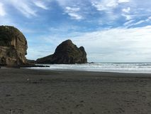 Piha Beach. In Auckland New Zealand. Black sand beach on the Tasman sea. Black sand with crashing surf in the background Stock Photography