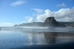 Piha beach in New Zealand. Piha beach with rock formations at the background in New Zealand royalty free stock image