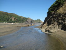 Piha Stream, Piha Beach, New Zealand. Piha Stream flowing into Tasman Sea royalty free stock image