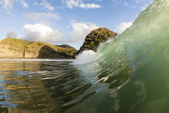 Piha Wave Tubing. A wave at Piha Beach, pitches out creating a hollow tube stock photography