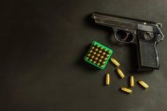 Piistol στο μαύρο υπόβαθρο Πυροβόλο όπλο και κασέτες στον πίνακα Δικαίωμα να κρατηθεί ένα πυροβόλο όπλο Στοκ φωτογραφία με δικαίωμα ελεύθερης χρήσης