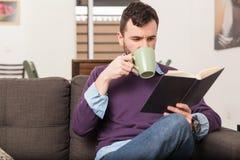 Pijący kawę i czytanie w domu zdjęcia stock