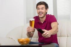 Pijący piwo i oglądać TV. Rozochoceni młodzi człowiecy pije piwo obrazy stock