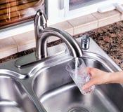 Pijący szkło wypełnia up z wodą kranową od kuchennego fauce zdjęcia stock