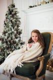 Pijama vestindo da menina que senta-se na poltrona envolvida em uma cobertura com fundamento do feriado pela árvore e pela chamin Fotografia de Stock