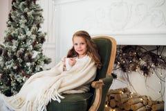 Pijama vestindo da menina que senta-se na poltrona envolvida em uma cobertura com fundamento do feriado pela árvore e pela chamin Imagens de Stock Royalty Free