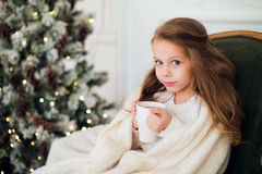 Pijama vestindo da menina que senta-se na poltrona envolvida em uma cobertura com fundamento do feriado pela árvore e pela chamin Fotografia de Stock Royalty Free
