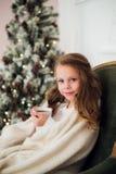 Pijama vestindo da menina que senta-se na poltrona envolvida em uma cobertura com fundamento do feriado pela árvore e pela chamin Fotos de Stock