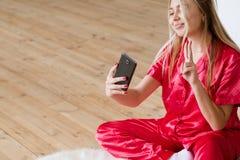 Pijamas de la mujer del apego del smartphone del hábito de Selfie foto de archivo libre de regalías