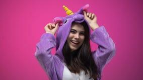 Pijamas del unicornio de la mujer que llevan caucásica que se divierten aislada en fondo rosado almacen de video