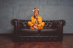 Pijamas para Halloween bajo la forma de jirafa Retrato emocional de una muchacha en un fondo del sofá Hombre loco y divertido en  foto de archivo