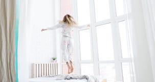 Pijamas que llevan baile de la mujer joven, feliz, saltando en cama en su dormitorio en casa almacen de metraje de vídeo