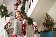 Pijamas que llevan de la familia emocionada que corren abajo de las escaleras que sostienen medias el mañana de la Navidad fotos de archivo