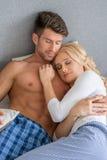 Pijamas que llevan de los pares que se acurrucan en cama imagenes de archivo