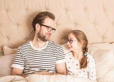 Pijamas que llevan del padre y de la hija en una cama imágenes de archivo libres de regalías