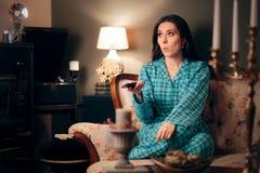 Pijamas vestindo da menina que olham a tevê em sua sala fotos de stock