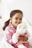 Pijamas vestindo da moça na cama com brinquedo peluches Imagem de Stock