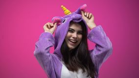 Pijamas vestindo do unicórnio da mulher caucasiano que têm o divertimento isolado no fundo cor-de-rosa video estoque