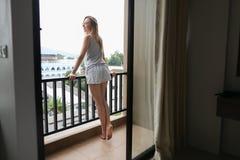 Pijamas vestindo do verão da mulher bonita nova que estão no balcão e que olham construções fotos de stock royalty free