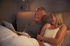 Pijamas vestindo dos pares superiores que encontram-se na cama que olha o portátil foto de stock royalty free