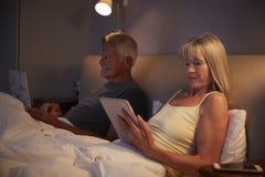 Pijamas vestindo dos pares superiores que encontram-se na cama usando dispositivos de Digitas fotos de stock royalty free