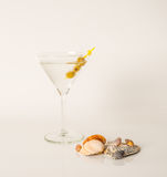 Pije w Martini szkle, Martini napój z zielonymi oliwkami, seashel Zdjęcie Stock