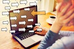 Pijl die in de tegenovergestelde richting met de mens gaan die laptop met behulp van royalty-vrije stock foto's